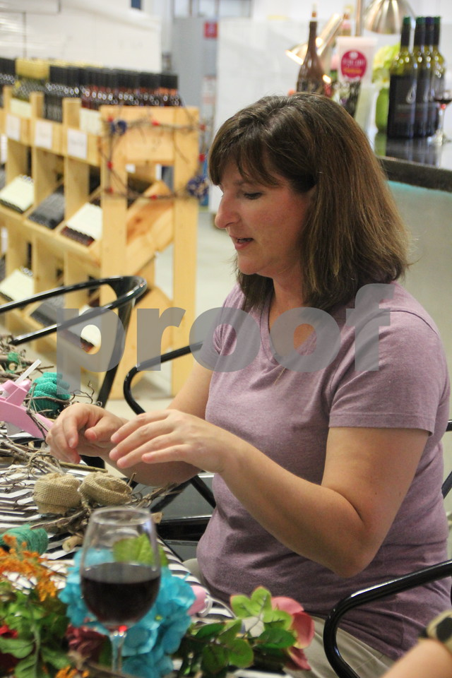 Krista Leigh is one of  the ladies who attended  craft night at Soldiers Creek Winery on Thursday, July 16, 2015. She is seen here  working on her  square wreath she is creating.