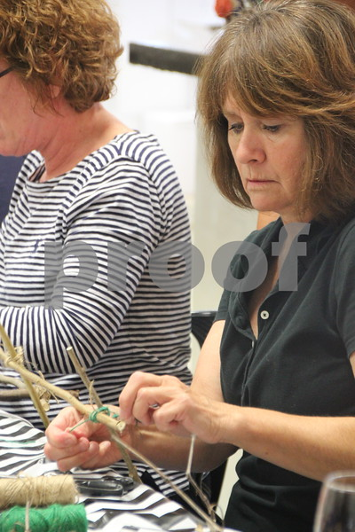 Sue Hrabak applies some string to her craft project to hold it together. She was a participant in the Soldiers Creek Winery  craft night held there on Thursday, July 16, 2015.
