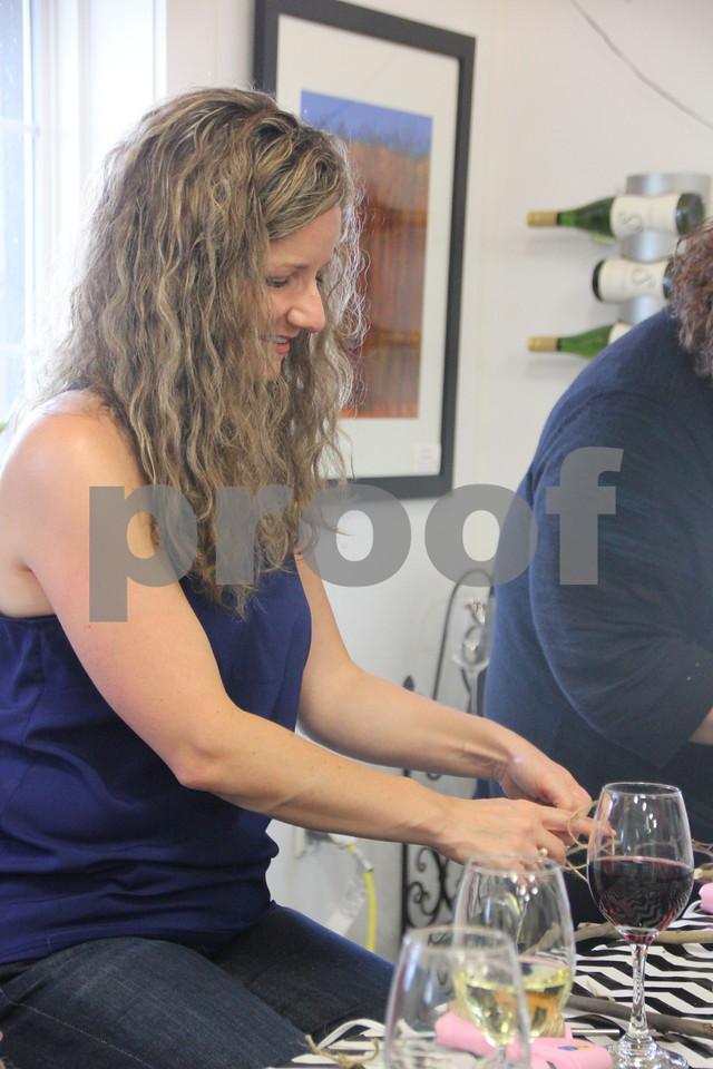 Katie Buechler assembles her craft project at the Soldiers Creek Winery's Un'Wine'd craft night event held there on Thursday, July 16, 2015.