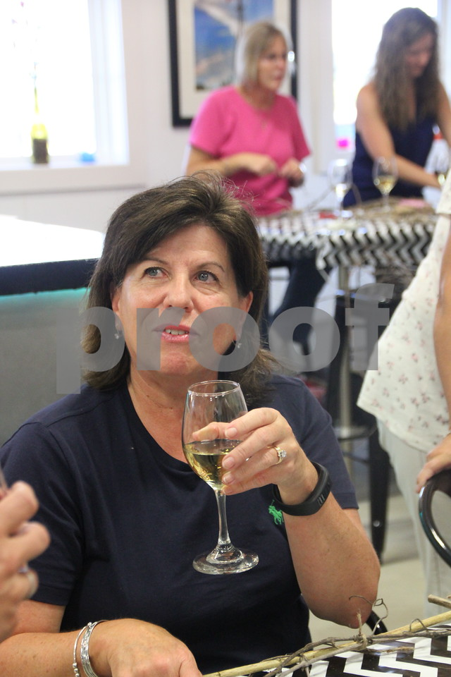 Jan Moeller samples some of the wine available at the Soldiers Creek Winery where the craft night was being held on Thursday, July 16, 2015. She was also one of the participants  making a craft project that night.