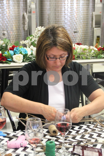 Tina Cooper puts more  of her craft project together at the Soldiers Creek Winery's Un'Wine'd craft night event held there on Thursday, July 16, 2015.