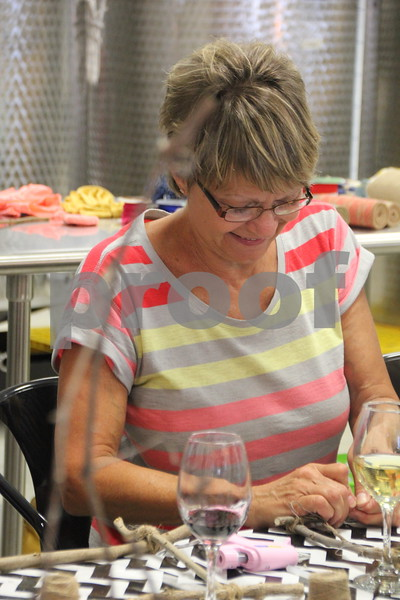 Carol Pederson applies more decoration to her craft project  she is making at the Un'Wine'd  craft night held at Soldiers Creek Winery on Thursday, July 16, 2015.