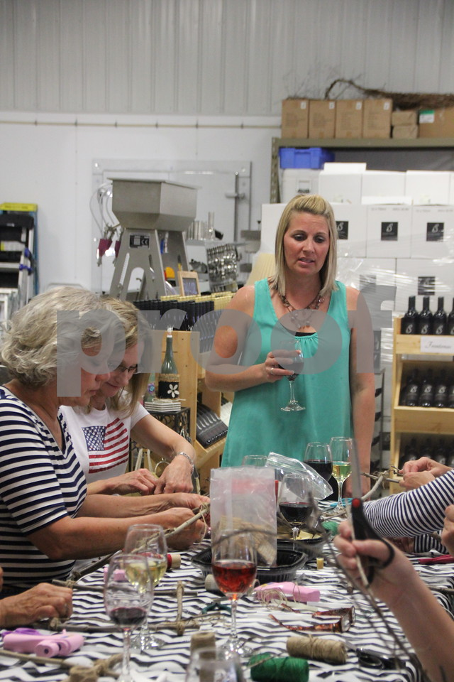 Annie Wolfe (in the blue shirt and standing) instructs  the ladies in attendance on how to make a craft project.  The ladies were participants in the Soldiers Creek Winery Un'Wine'd craft night held there on Thursday, July 16, 2015.