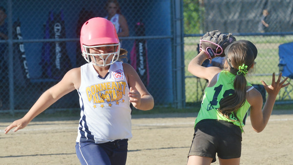 WARREN DILLAWAY / Star Beacon HANNAH STILTNER (left) of Conneaut races to first  base as Nikki Griffith of Ashtabula waits for the ball on Thursday evening during minor league all-star action at Cederquist Park in Ashtabula.