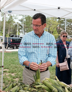 071816  Wesley Bunnell | Staff  Governor Dannel Malloy visited the downtown New Britain CT fastrak station which features a farmers market on Monday afternoons. Governor Malloy sorts through ears of corn.