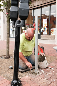 071416  Wesley Bunnell | Staff  Jason Dionne from Martin Laviero Contractors is shown in the process of moving parking meters further back from the curb on Main St on Thursday afternoon.  Complaints were made that the meters were too close to the curb and easily prone to being hit by parking cars.