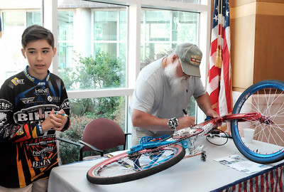 "071516  Wesley Bunnell | Staff  10 year old Johnny ""Hot Rod"" Tomboly, a competitive BMX racer on a national BMX race team has dedicated his 2016 season to all military & first responders. His goal is to have 1,000 signatures on his custom painted red,white & blue BMX bike by the 15th anniversary of the terrorist attacks on 9/11.  Army Veteran Don Van Garder, right, signs the bike with Johnny on the left."