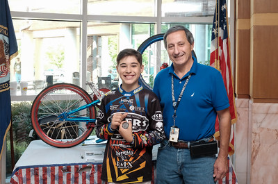 "071516  Wesley Bunnell | Staff  10 year old Johnny ""Hot Rod"" Tomboly, a competitive BMX racer on a national BMX race team has dedicated his 2016 season to all military & first responders. His goal is to have 1,000 signatures on his custom painted red,white & blue BMX bike by the 15th anniversary of the terrorist attacks on 9/11.  From L Johnny Tomboly with Assistant Chief of Voluntary Service Joe Canzanella."