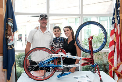 "071516  Wesley Bunnell | Staff  10 year old Johnny ""Hot Rod"" Tomboly, a competitive BMX racer on a national BMX race team has dedicated his 2016 season to all military & first responders. His goal is to have 1,000 signatures on his custom painted red,white & blue BMX bike by the 15th anniversary of the terrorist attacks on 9/11.  From L, John Tomboly, Johnny Tomboly & Sandra Tomboly."