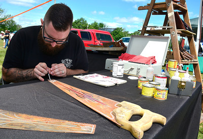 7/2/2016 Mike Orazzi | Staff Brenden Gingras paints on a wood saw at the Hand Painted Sign tent during the 11th annual Rumblers Nomads RUMBLE IN THE COUNTRY Car and Bike Show at the Terryville Fairgrounds Saturday morning.