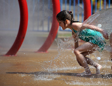 7/21/2016 Mike Orazzi | Staff Faith Close cools off in the Rockwell Park spray park during Friday's heat in Bristol.