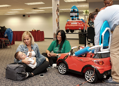 072916  Wesley Bunnell | Staff  Larimar Gonzalez holds her son Elijah Luciano, age 2, as the finishing touches are put on his customized electric car as Elijah's grandmother Zaina Lopez looks on. Children with disabilities, and their families, were presented with modified toy cars by middle school through college age technology students on Friday July 29th at the CCSU  ITDB building.