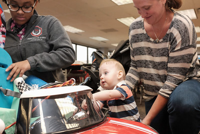 072916  Wesley Bunnell | Staff  Michael Ramsdell, age 13 months, being held by mom Amanda Ramsdell as he plays with his new electric car. Children with disabilities, and their families, were presented with modified toy cars by middle school through college age technology students on Friday July 29th at the CCSU  ITDB building.