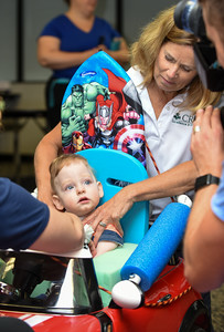 072916  Wesley Bunnell | Staff  Michael Ramsdell, age 13 months, is fitted for safety in his new customized electric car. Children with disabilities, and their families, were presented with modified toy cars by middle school through college age technology students on Friday July 29th at the CCSU  ITDB building.