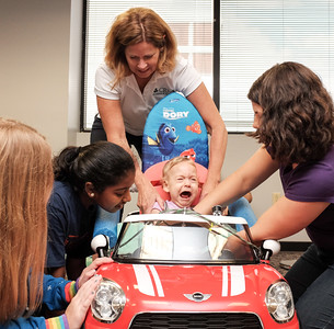 072916  Wesley Bunnell | Staff  Lisa Costen, right, helps place daughter Alicia Badowski, age 13 months, into her new electric car for the final customized measurements. Children with disabilities, and their families, were presented with modified toy cars by middle school through college age technology students on Friday July 29th at the CCSU  ITDB building.