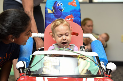 072916  Wesley Bunnell | Staff  Alicia Badowski, age 13 months, sits in her new custom fitted electric car. Children with disabilities, and their families, were presented with modified toy cars by middle school through college age technology students on Friday July 29th at the CCSU  ITDB building.