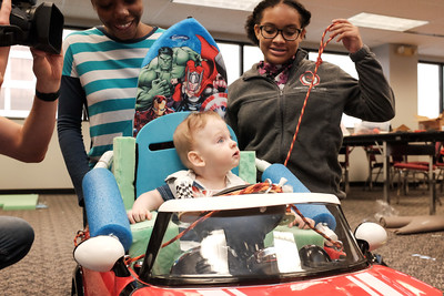 072916  Wesley Bunnell | Staff  Michael Ramsdell, age 13 months, gets ready to take his new electric car for a drive. Children with disabilities, and their families, were presented with modified toy cars by middle school through college age technology students on Friday July 29th at the CCSU  ITDB building.