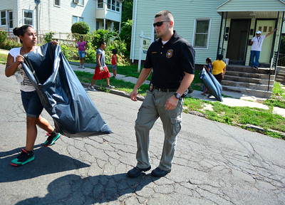 7/30/2016 Mike Orazzi | Staff New Britain Police Officer Miek Beebe and Jaritza Villa during a clean up of the North Oak Neighborhood in New Britain Saturday morning as part of North Oak NRZ 2nd Community Cleanup.