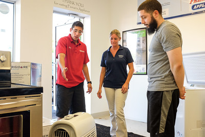 070516  Wesley Bunnell | Staff  Window & portable air conditioners as well as air conditioner service calls are keeping Ferrari's Appliance of Newington busy in the summer heat.  From L are Ray Rodriguez, store manager, owner Stacey Ferrari & customer Nick Burgio of Kensington.