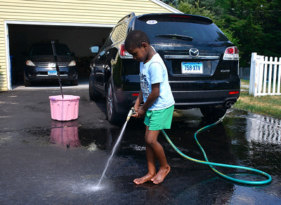 7/6/2016 Mike Orazzi | Staff Donovan Durham while washing one of the family cars on Baldwin Drive in Bristol Wednesday.