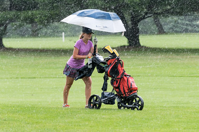 070716  Wesley Bunnell | Staff  Stanley Golf Course held day two of the PGA CT Section Jr. Golf Tournament on Thursday. Jenna Schwab, age 14, of Bristol fights to stay dry on her walk back to the clubhouse after play was suspended due to rain.