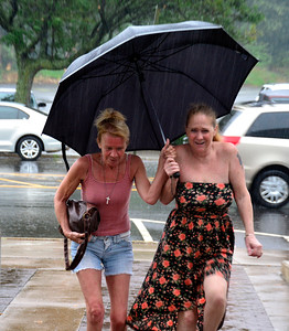 7/7/2016 Mike Orazzi | Staff Sue Waag and Donna Cyr attempt to stay dry while crossing North Main Street during a sudden rainfall Thursday.