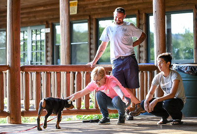 063016  Wesley Bunnell | Staff  Kindergarten Puppy Training Class was held on June 30 at Pistol Creek Golf Course in Berlin. Linda Daresco of Portland kneels with open arms for her 12 week old Doberman puppy named Kaine along with Tim Aresco, standing, and Javier Mercedo.