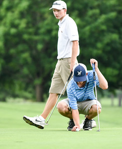 070716  Wesley Bunnell | Staff  Stanley Golf Course held day two of the PGA CT Section Jr. Golf Tournament on Thursday. Golfers wait on the fairway for news on play being delayed due to rain. Paul Wheatley, age 17, of Wethersfield replaces his mark with his ball on the 9th green with Jack Snyder, age 17, of Ellington walks behind him.