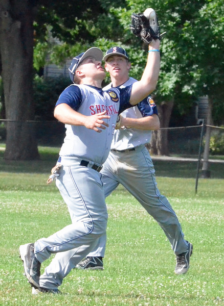 KYLE MENNIG - ONEIDA DAILY DISPATCH Sherrill Post's John Bickom (10) catches a fly ball in left field in front of teammate Mitch DeBarr to retire an Adrean Post batter during their American Legion Baseball District 5 playoff game in Sherrill on Sunday, July 17, 2016.