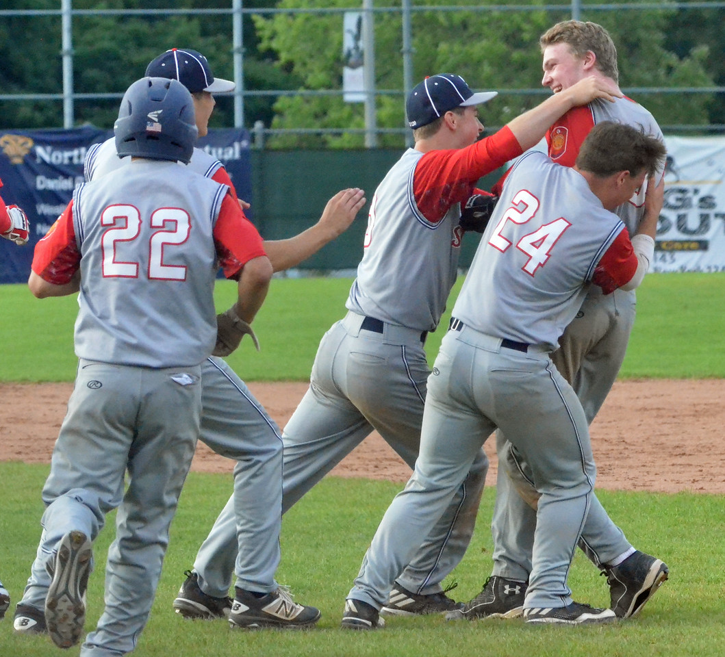 KYLE MENNIG – ONEIDA DAILY DISPATCH Sherrill Post's Davey Moffett is mobbed by his teammates after his game-winning hit against Binghamton Post during their American Legion Baseball State Championship tournament game in Utica on Tuesday, July 25, 2017.