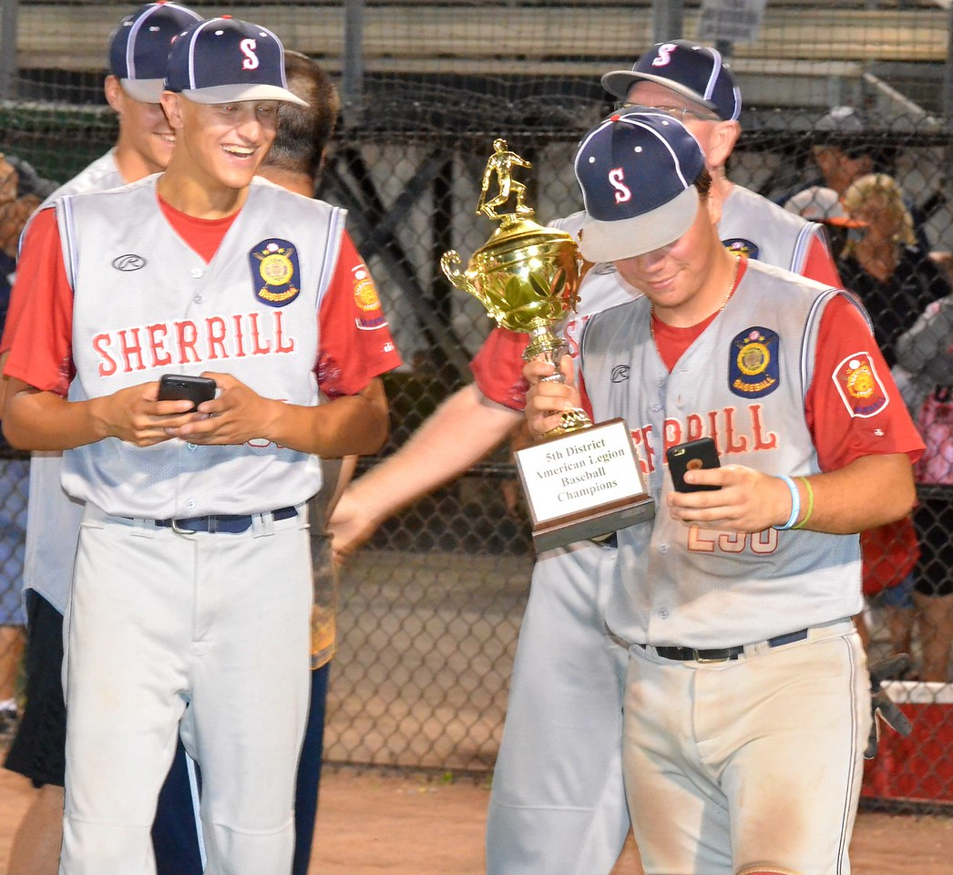 KYLE MENNIG – ONEIDA DAILY DISPATCH Sherrill Post's Tyler Rotach takes a selfie with the trophy after winning the American Legion Baseball District 5 championship in Utica on Friday, July 21, 2017.