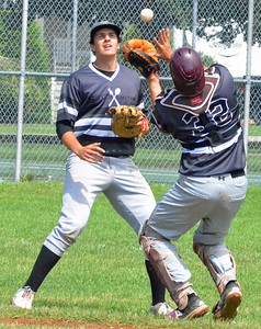 KYLE MENNIG – ONEIDA DAILY DISPATCH Sherrill Silversmiths catcher Vincent Timpanelli moves under a pop fly to make a catch and retire a Cortland Crush batter during their game in Sherrill on Saturday, July 15, 2017. Looking on is teammate Craig Sandford.