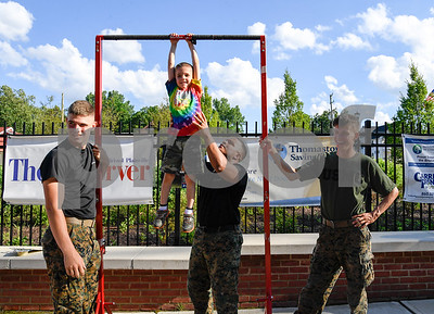 070317  Wesley Bunnell | Staff  The Bristol Blues held military appreciation night at Muzzy Field on Monday evening. Christopher Bourgoin, age 5, tries his hand at pull ups at the Marine Corps table with help from Sgt. Jesus Torres, Lance Corporal Michael Marotta, left stands along with Pfc Jeremiah Holm.