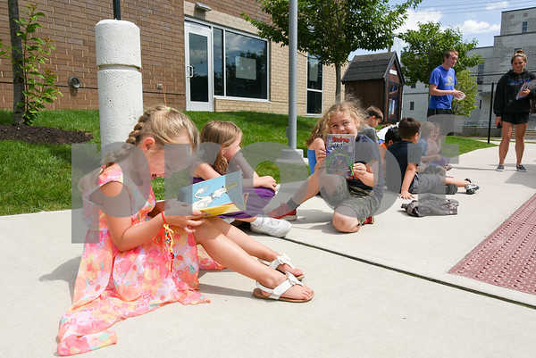 070517 Wesley Bunnell | Staff Rylee Keeley, age 6, reads One Fish, Two Fish, Three Fish, Blue Fish by Dr. Seuss outside of the Bristol Boys and Girls Club as she sits next to Lyla Bray, age 5, and Jack Lyon, age 6, holding his book for the camera. The books are from the Bristol Board of Education Book Mobile which made a visit to the club.