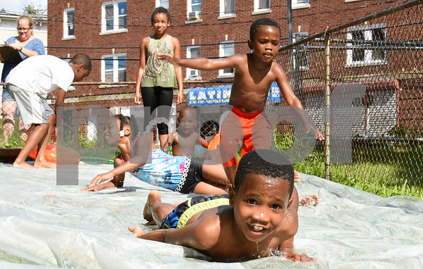 071717 Wesley Bunnell | Staff Beating the heat on Monday afternoon with a home made slip n slide is Zion Cummings, age 6, along with Kainan Cummings, age 4 and Tiffany Bryant, age 11.