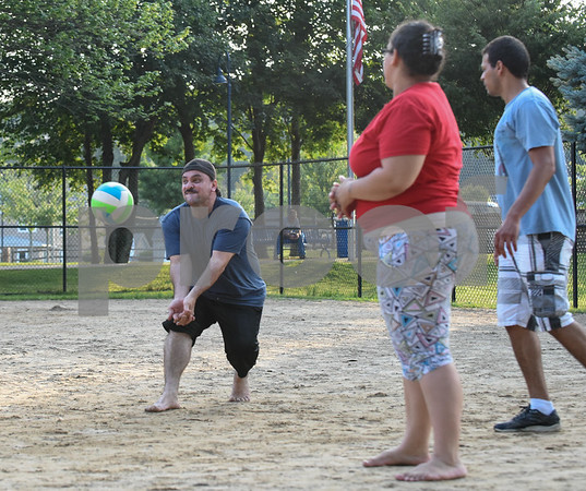 071717 Wesley Bunnell | Staff Julio Aponte returns a serve in a game of sand volleyball at Casey Field in Bristol on Monday evening. Teammates are Cassandra Roa and Carlos Rodriguez.