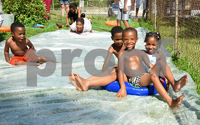 071717  Wesley Bunnell   Staff  Shamar Lebby, R age 5, leads the way down a home made slip n slide on a hot Monday afternoon along with Tiffany Bryantne, age 8, Zion Cummings, age 6 and Kainan Cummings, age 4 on the left.