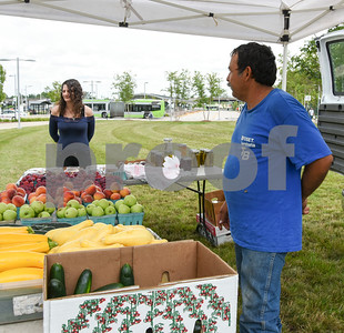 071717  Wesley Bunnell   Staff  Monday afternoon marked the first farmers' market of the year at the New Britain Fastrak location with a stand from Dondero Orchards. Amanda Palmisano looks over the selection as Alberto Hernandez of Dondero stands to the right.