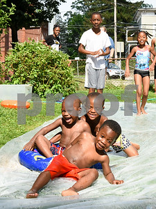 071717  Wesley Bunnell   Staff  Beating the heat on Monday afternoon with a home made slip n slide Kainan Cummings, age 4, slides down a home made slip n slide along with Zayvion Robinson, age 2, Shamar Lebby, age 5, as Taushan Bryante, age 11 and Tiffany Bryant, age 8, stand in the background.
