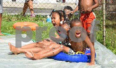 071717  Wesley Bunnell   Staff  Tiffany Bryant, age 8, L, and Shamar Lebby, age 5, react to having cold water poured on them while sitting on a home made slip n slide.