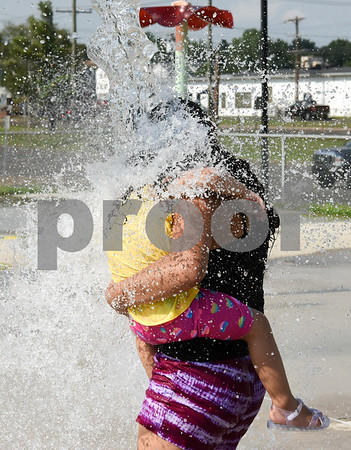 072017 Wesley Bunnell | Staff Abneliz Alamo, age 13, holds Liushka Arroyo, age 2 as water pours out of one of the several buckets at the Chesley Park Splash Pad on Thursday afternoon.