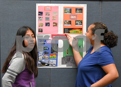 072117  Wesley Bunnell   Staff  Middle and High School students completed a two week CCSU TRiO program with presentations and awards on Friday afternoon. Michelle Montero, L, and partner Julyssa Garcia look over their project on deep sea exploration.