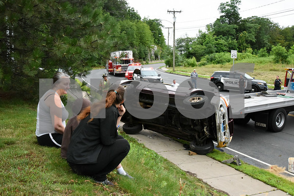 072417 Wesley Bunnell   Staff Emergency crews responded to a pick up truck rollover on Mountain Rd in Bristol on Monday afternoon. The driver, L, sits with family as they watch the truck pushed back onto its tires by the tow truck.