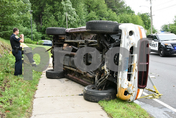 072417 Wesley Bunnell   Staff Emergency crews responded to a pick up truck rollover on Mountain Rd in Bristol on Monday afternoon. A police officer takes photos of the truck.