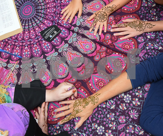 072517 Wesley Bunnell | Staff Jamilah Zebarth paints henna on the hand of Keri Kemish as her daughters Brooke and Paige wait at the Berlin-Peck Memorial Library on Tuesday evening.