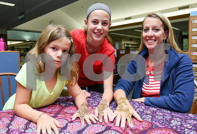 072517  Wesley Bunnell | Staff  Brooke, age 8, Paige, age 11, and their mother Keri Kemish after having henna applied to their hands by Jamilah Zebarth at the Berlin-Peck Memorial Library on Tuesday evening.