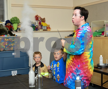 072617  Wesley Bunnell | Staff  Eric from Scientellers works with volunteers Ryan Ahlgren, age 4 L, and Isaac Morehouse, age 6, during a smoke making experiment at the Bristol Library on Wednesday evening.