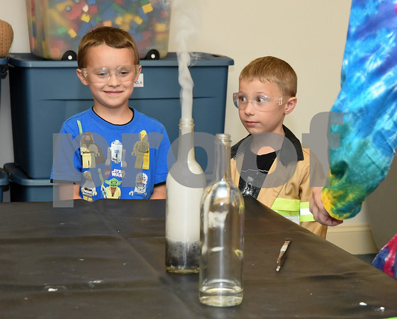 072617 Wesley Bunnell | Staff Isaac Morehouse, age 6, and Ryan Ahlgren, age 4, volunteered to help Eric from Scientellers during a smoke making experiment at the Bristol Library on Wednesday evening.