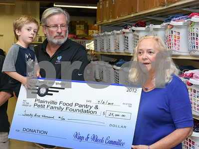 073117  Wesley Bunnell | Staff  Plainville Wings and Wheels presented a check to benefit the Plainville Community Food Pantry and the Petit Family Foundation on Monday evening at the Plainville Community Food Pantry.  Representative William Petit Jr. holds son William Petit III as they stand next to President of the Board of Directors for the Plainville Community Food Pantry Maggie Carlin.