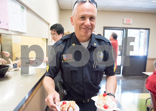 071217 Wesley Bunnell   Staff New Britain TRIAD served up ice cream at the New Britain Senior Center on Wednesday afternoon. New Britain Police Sgt. Art Powers walks two sundaes to a table.